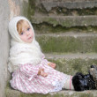 The small sad girl in a white scarf sits on a ladder — Stock Photo