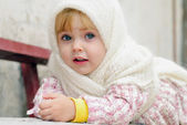Portrait of the small beautiful girl in a white scarf on a bench — Stock Photo