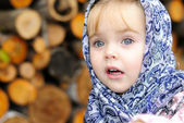 Portrait of the small beautiful girl in a dark blue scarf — Stock Photo