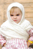 The small beautiful angry girl in a white scarf at a fence — Stock Photo