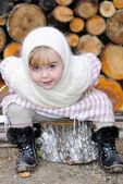 Beyaz kaşkollu küçük korkunç kız kenevir üzerinde oturur — Stok fotoğraf