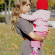 The young beautiful girl with the small child in autumn park — Stock Photo #9374431