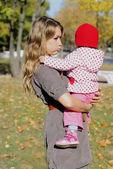 La giovane ragazza bella con il bambino piccolo nel parco d'autunno — Foto Stock