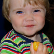 Small year-old child smiles and eats orange — Stock Photo #9387970
