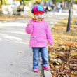 Small girl walks in autumn park — Stock Photo