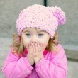 Portrait of the small beautiful surprised girl with in a pink ca — Stock Photo