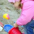 Stock Photo: The small beautiful girl in pink clothes plays sand