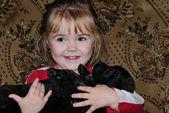 Malá krásná dívka s malé černé štěně — Stock fotografie