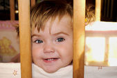 Small beautiful child sits in baby child's bed — Photo