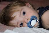 小さな美しい子乳首とベッドにかかっています。 — ストック写真