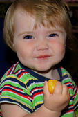 Small year-old child smiles and eats orange — Stock Photo