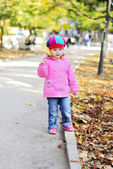Small girl walks in autumn park — Stok fotoğraf