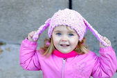 Portrait of the small beautiful girl with in a pink cap with ear — Stock Photo