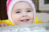 The small beautiful girl looks out behind a parapet — Stockfoto