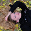 Stock Photo: The young beautiful girl lies on a green grass with yellow leave