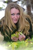 年轻漂亮的女孩在绿色草地上说谎与黄色假 — 图库照片