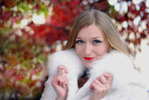 The young beautiful girl in a white fur coat with red lipstick — Stock Photo