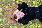 Młoda piękna dziewczyna znajduje się na zielonej trawie z urlopu żółty — Zdjęcie stockowe