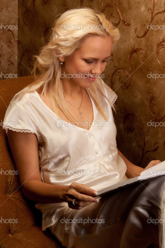 Young and beautiful girl reading a book cover in black sitting on a couch in his home — Stock Photo #8893838