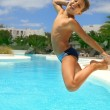 Boy jumping into the pool smiling — Stock Photo #9169264