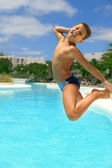 Boy jumping into the pool smiling — Stock Photo