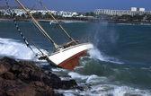 Yacht crash on the rocks in stirmy weather — Stock Photo