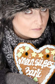 Woman with gingerbread heart — Stock Photo