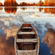 Wooden boat in the lake with the reflection of clouds - Stock Photo