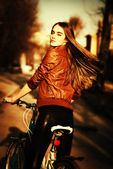 Portrait of pretty young woman with bicycle in a city road — Stock Photo