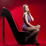 Beautiful woman sitting on the red high heel women shoe sofa — Stock Photo #10124717