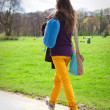 Young woman walking on path in city park — Stock Photo