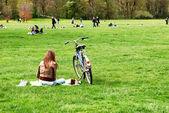 Bella ragazza con una bicicletta poggia su un erba al parco della città — Foto Stock