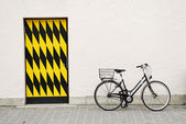 Old city bike againtst a big wall with door — Stock Photo