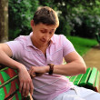 A young man looks at his watch on his arm and sits on a bench in the park and waiting for meeting — 图库照片
