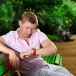 A young man looks at his watch on his arm and sits on a bench in the park and waiting for meeting — Stock Photo #10434947