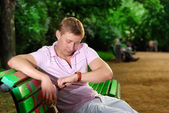 A young man looks at his watch on his arm and sits on a bench in the park and waiting for meeting — Stock Photo