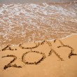 Inscription 2011 and 2012 on a beach sand — Stock Photo