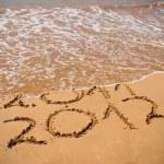 Inscription 2011 and 2012 on a beach sand — Stock Photo