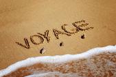 Inscription on wet sand voyage — Stock Photo