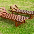 Two wooden sunbeds on the green grass lawn in hotel — Stock Photo #8130421