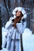 Smiling girl in a fur coat in the winter forest under snowfall — Stock Photo