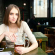 Girl with a glass of beer in the cafe — Stockfoto