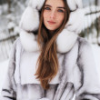 Close-up portrait of smiling girl in fur hood in winter city — Stock fotografie