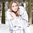 Young beautiful girl in fur smiling, and walking through the snow road — Stock Photo