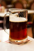 Mug of dark beer close up on table in cafe — Stock Photo