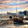Airplane in the airport loading bay - Stock Photo