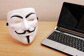 Annonymous mask and laptop on the table — Stock Photo