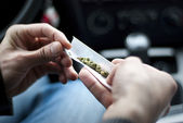 Man making joint and a stash of marijuana in the car — ストック写真