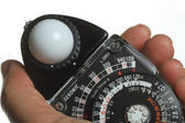 Lightmeter in a hand with white background — Stock Photo