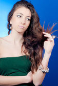 Young beautiful woman looking at her split hair — Stock Photo